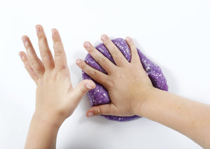Child's hands pushing into a ball of purple Rockstar slime from Messy Play Kits.
