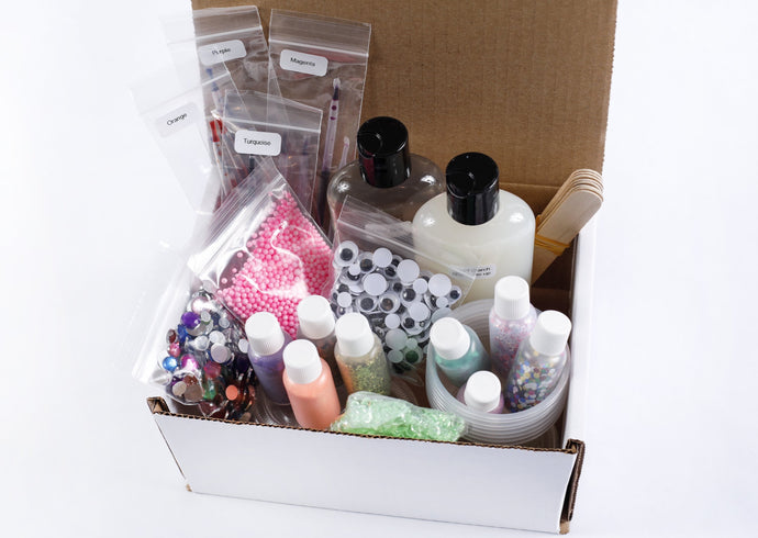 Box of slime making supplies including bottles of glue, liquid starch, pipettes of colors, mixing containers, stir sticks. Plus extra mix-ins like glitter, jewels, and googly eyes.