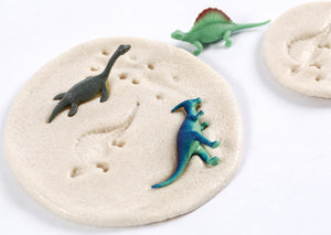 Close up of toy dinosaurs in dough, showing imprints that look like dinosaur fossils.