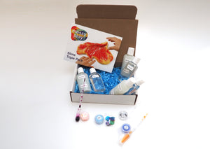 Contents of a Slime Triple Pack displayed around a box, including including a glue bottles, liquid starch bottles, glitter, and pipettes of color.