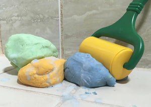 Playdough soap in three colors, green, yellow, and blue. Pictured with a play dough roller tool.