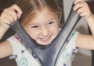Young girl smiling while stretching slime in front of her face.