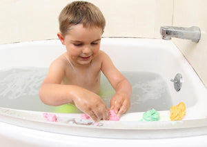 Child playing and molding playdough soap on the edge of a bathtub. Three colors of play dough soap including magenta, green, and yellow,