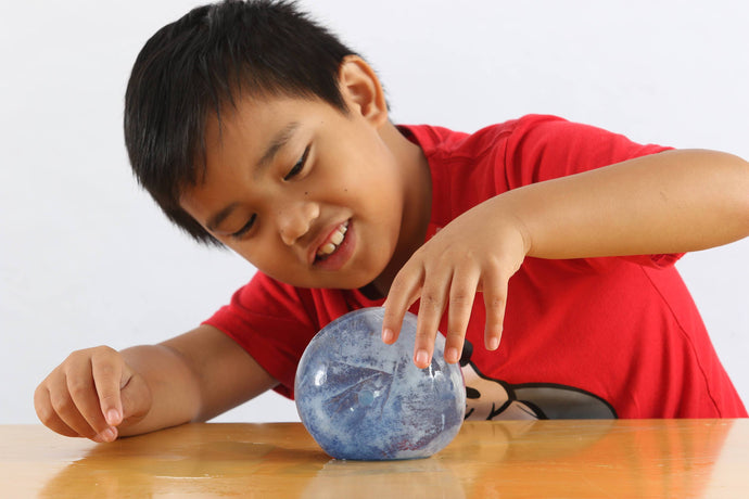 Boy examining round ball of ice in the density experiment in the Under the Sea Messy Play Kit,