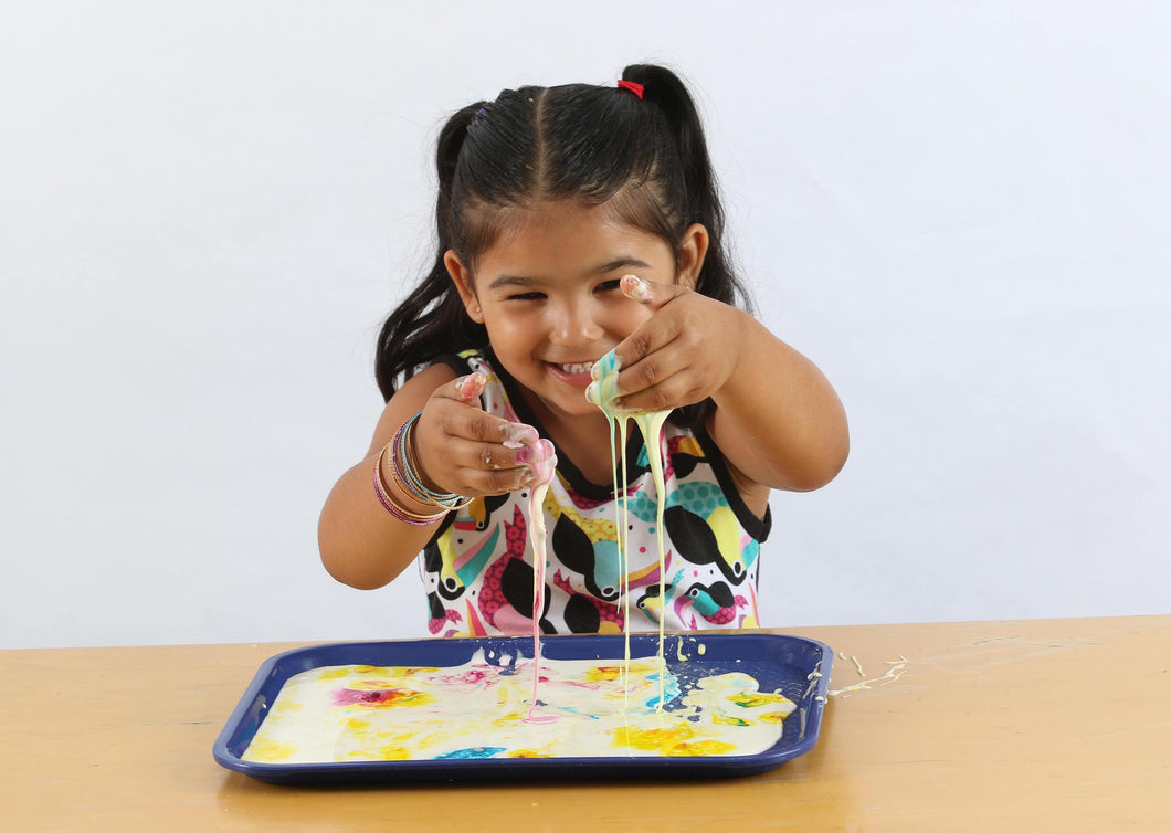 Smiling girl dipping her hands in colorful ooze from the colorburst oobleck activity.