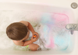 Child in bathtub playing with spray bottle from Bath Tub Fun Messy Play Kit, top view