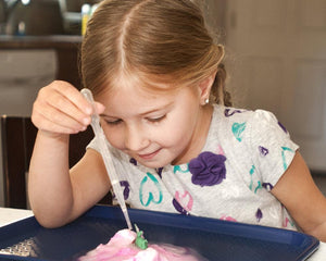 Girl using a pipette to drip liquid onto a dinosaur egg to make it hatch a toy dinosaur.