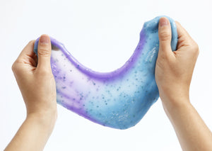 Two hands stretching Messy Play Kit's color-changing Mermaid slime that changes from blue to purple in the sunlight