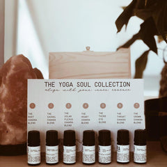 "7 essential oil bottles in a row in front of a ""yoga soul collection"" chart which is leaned against a wooden box. A large crystal is in the background on the left."