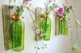 Green bottle attached to a wall with flowers inside