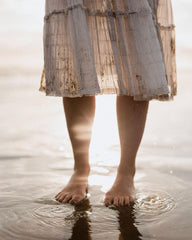 Woman's legs standing in shallow sea water wearing a floaty dress with sun shining on the water's reflection.