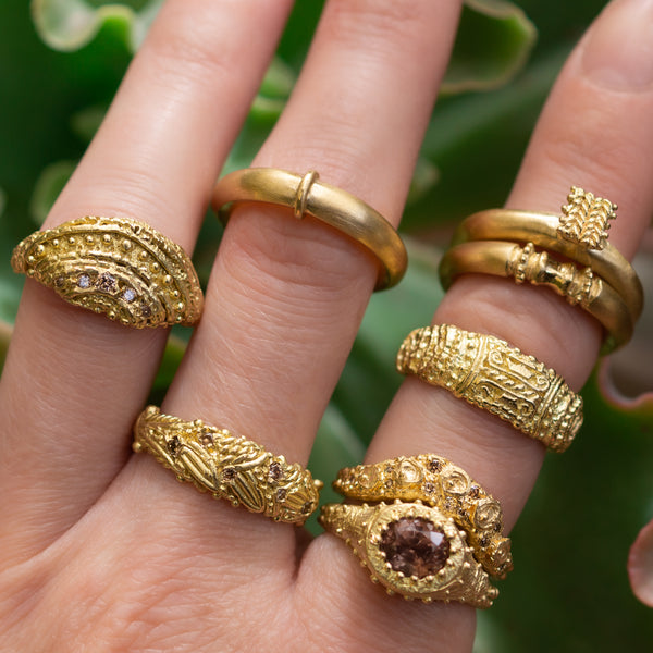 Rings from Fiona Fitzgerald Jewellery's Anamnesis Collection, worn on a hand with green background