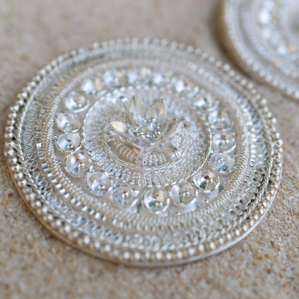 Detail of granulation and filigree on Sulis Earrings in fine silver and sterling silver by Fiona Fitzgerald Jewellery photographed on sand