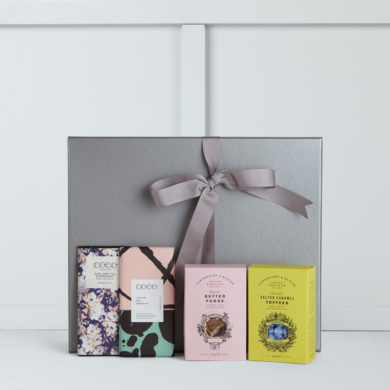 This gift box includes Salted Caramel Toffee & Butter Fudge by Cartwright & Butler, Earl Grey Tea & Bergamot Dark Chocolate Bar & Lavender Milk Chocolate Bar by Coco Chocolatier