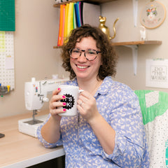 leah at her desk holding a coffee mug