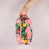 floral double zip toiletry case being held by a hand