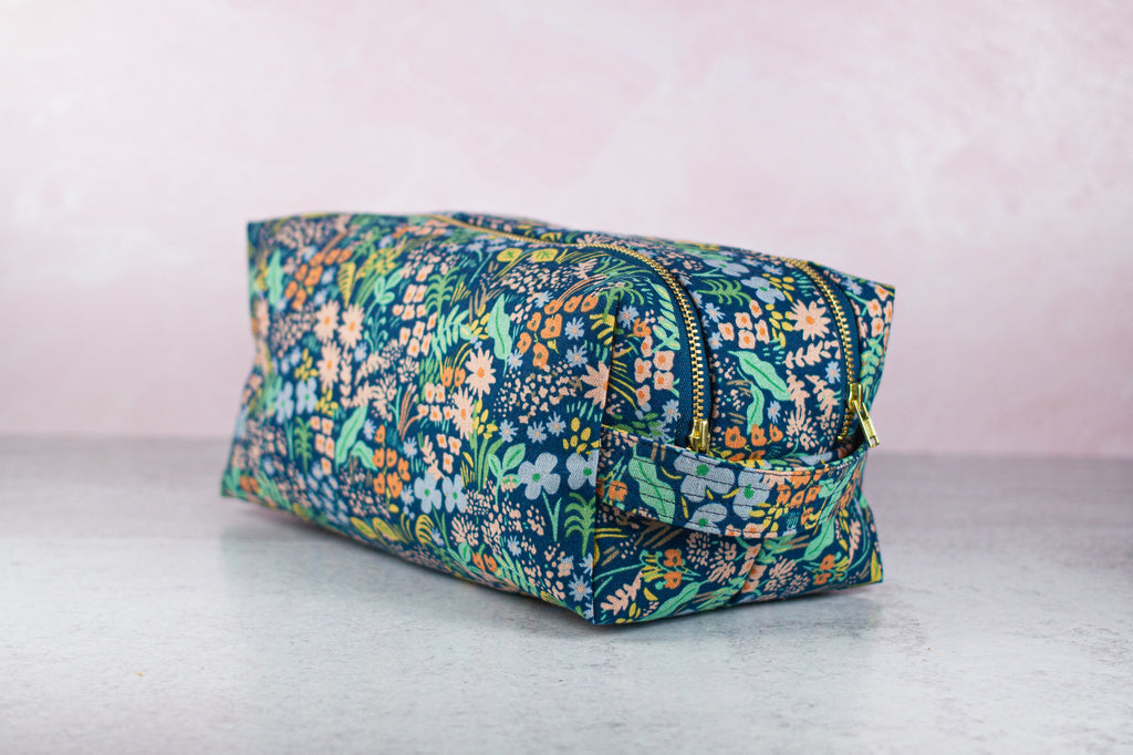 a blue floral toiletry case made by modern tally sitting on a surface