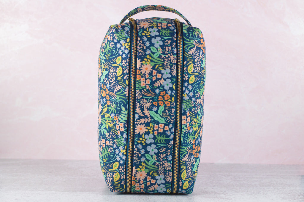 a large makeup bag made with rifle paper co fabrics stands on end, handle up