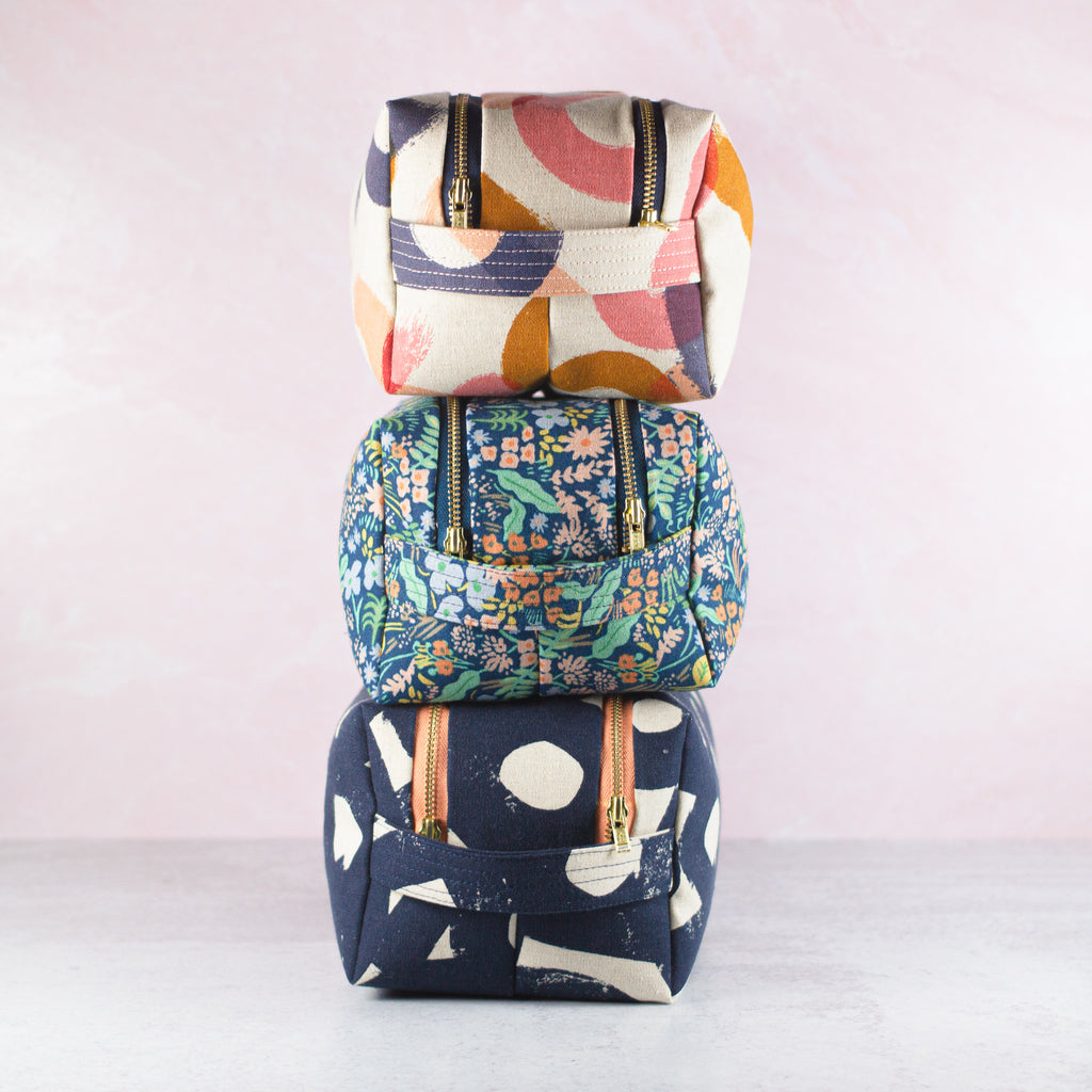 three large dopp kits in colorful patterns stacked on top of each other
