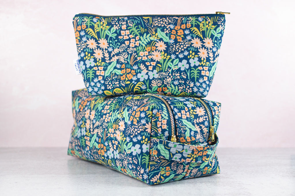 a blue floral makeup bag stacked on top of a matching dopp kit made by modern tally