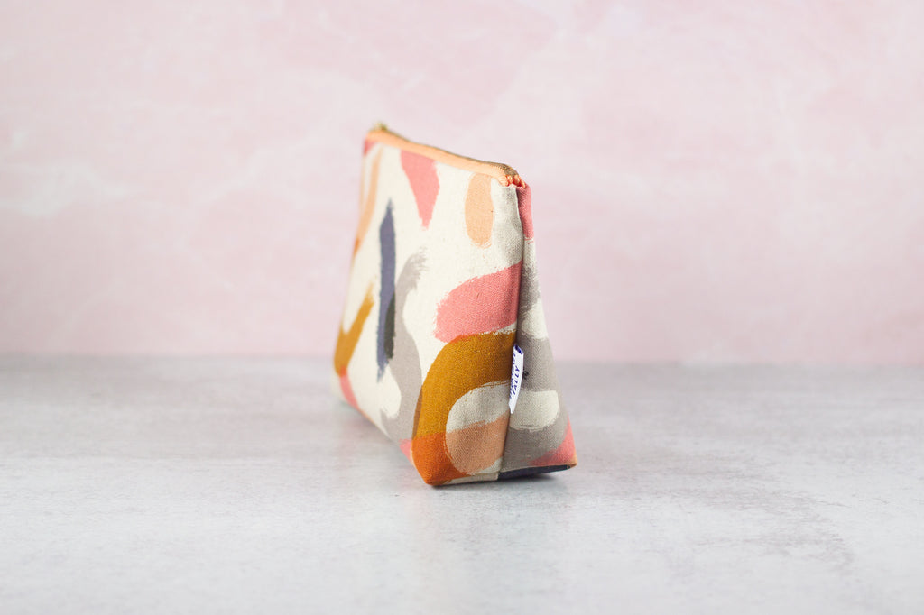 Side angle of zipper pouch in abstract brushstrokes