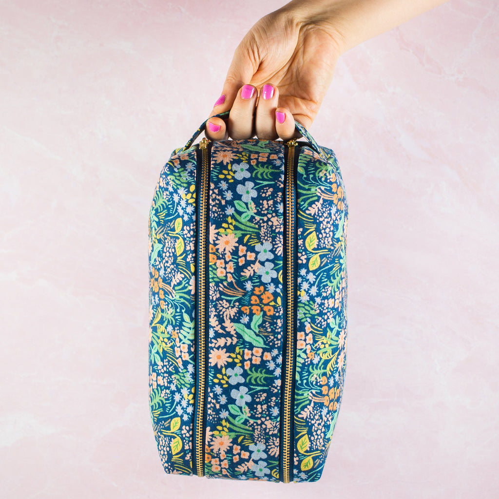 a hand holding a blue floral toiletry case made by modern tally