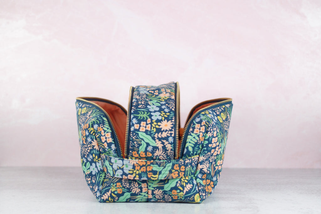 a blue floral toiletry case made by modern tally with zippers open, sitting on a surface