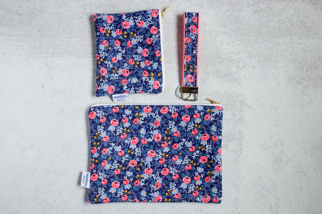 a matching set of large pouch, small pouch, and key fob laid out flat