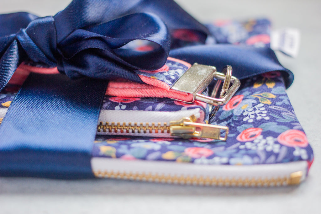 a close up view of a matching set of large pouch, small pouch, and key fob  tied with a ribbon