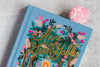close up of a beautifully illustrated copy of Anne of Green Gables with a neon pink bookmark in it
