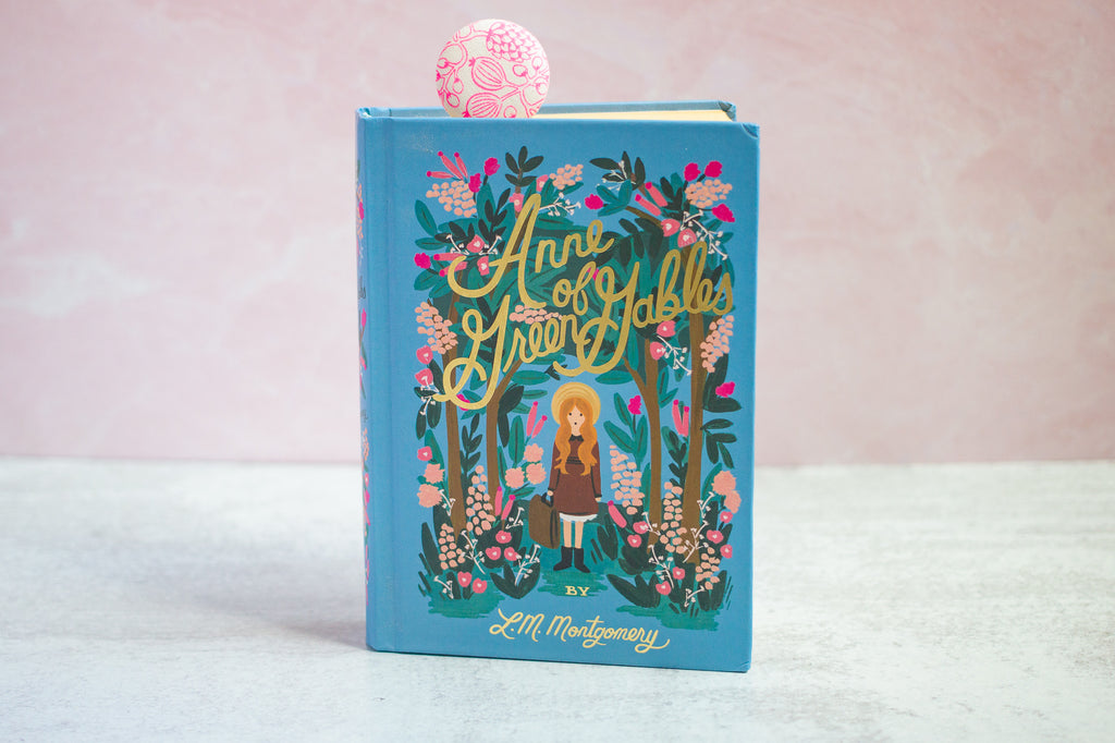 a beautifully illustrated Anne of Green Gables standing upright on a surface with a neon pink floral bookmark in it