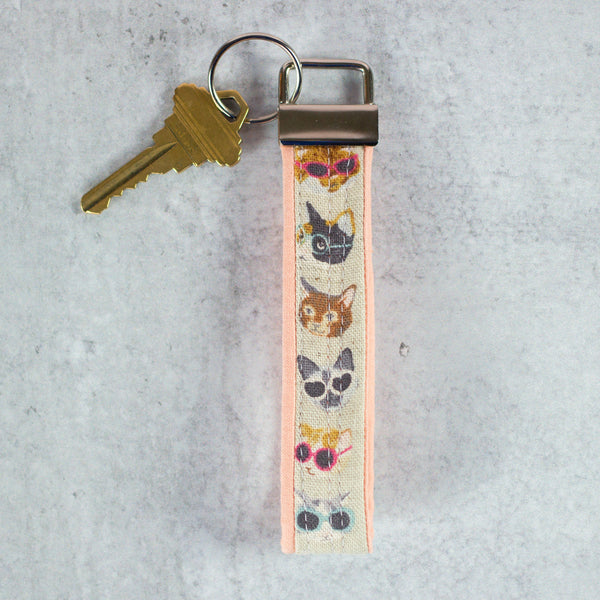 quilted key fob with a key attached and cats wearing sunglasses on the fabric