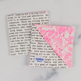 A corner bookmark with neon pink florals and black and white text laying on top of another one, backside up.