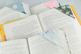 A group of books all laying open to a page marked with a patterned corner bookmark.
