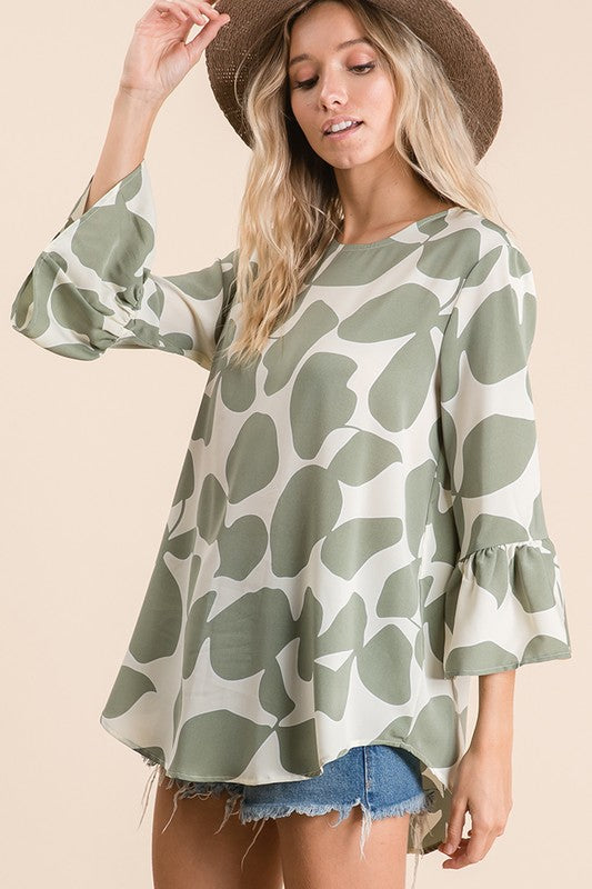 Printed bell sleeve blouse, featuring rounded neckline, key hole back and button closure, ruffle sleeves and high low shirt tail hem in a flattering loose fit body this piece will keep you looking fabulous and feeling comfortable!
