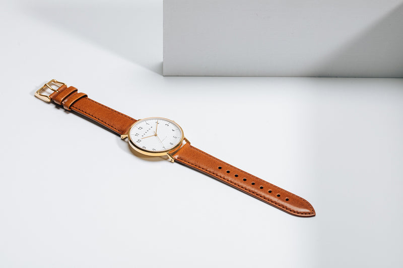 Gold watch with tan watch strap
