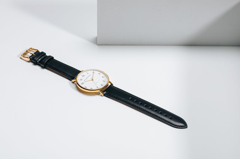 Gold watch with navy watch strap open