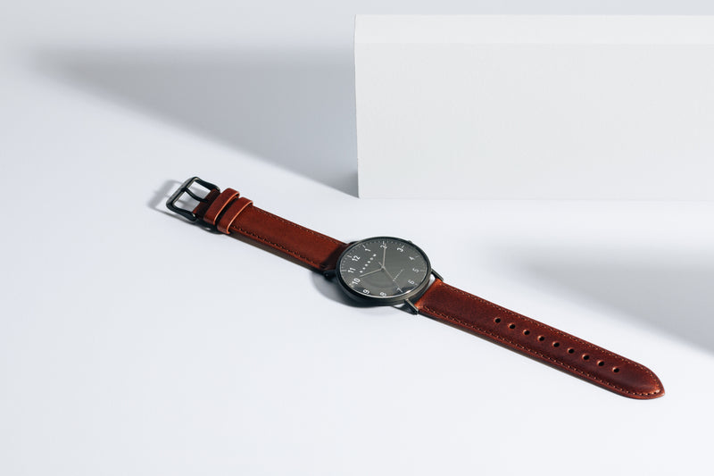 Black watch with tan watch strap open