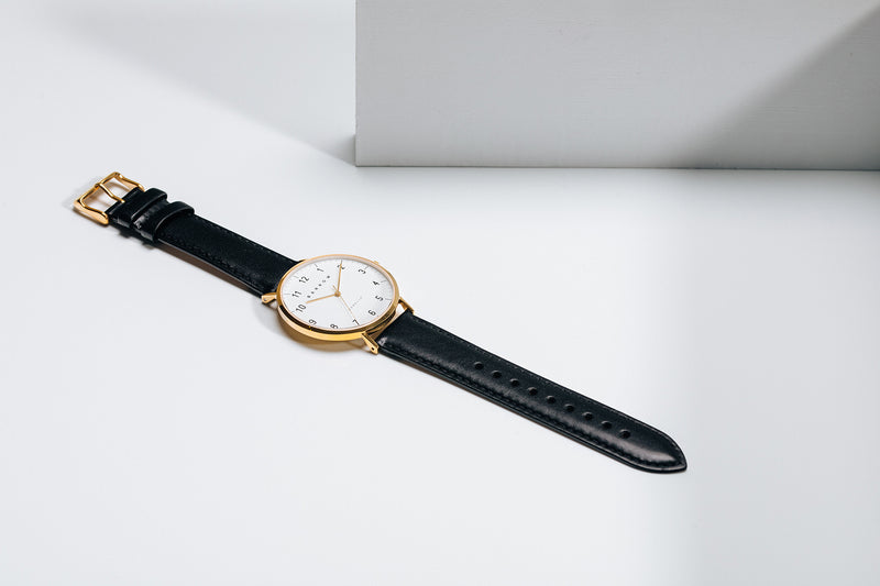 Gold watch with black watch strap open