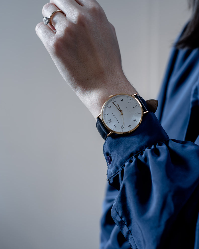 woman wearing Gold watch with navy watch strap