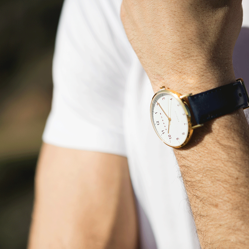 Man wearing Gold watch with black watch strap