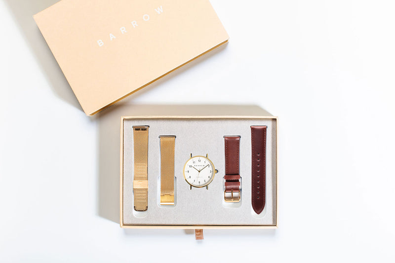 Gold watch in box with straps