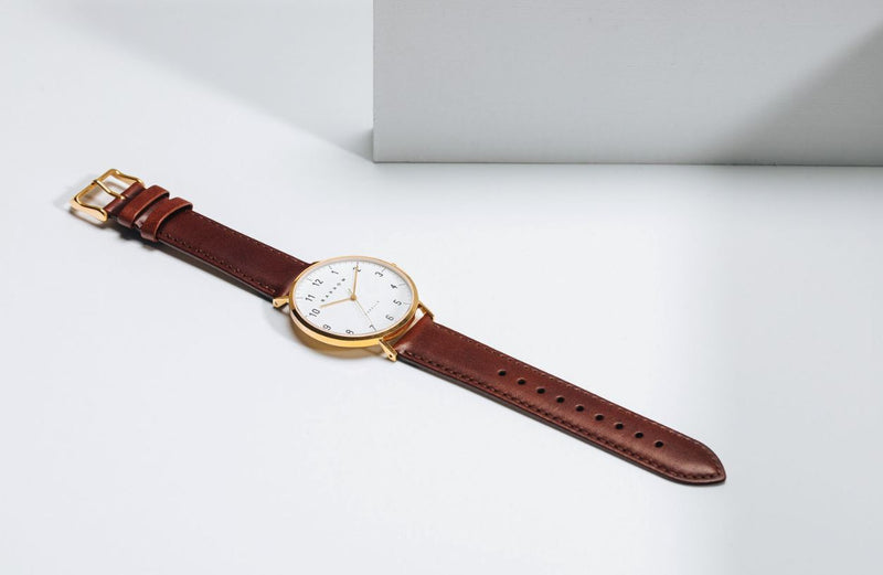 Gold watch with brown watch strap open