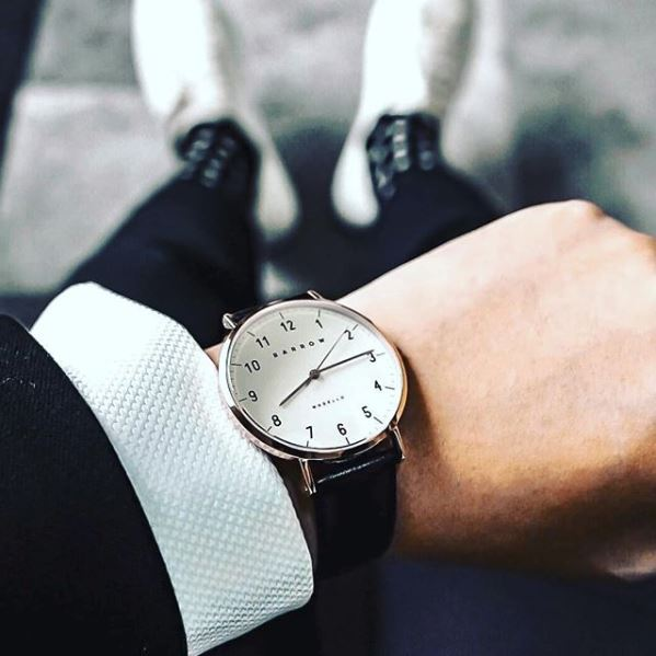 Man wearing silver watch with black watch strap