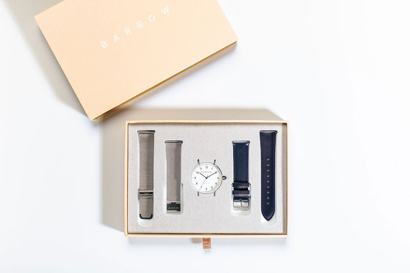 silver watch with navy watch strap in box