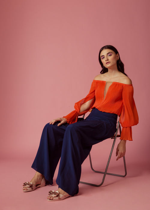 Orange pleated off-shoulder top with sheer neckline and drape sleeves