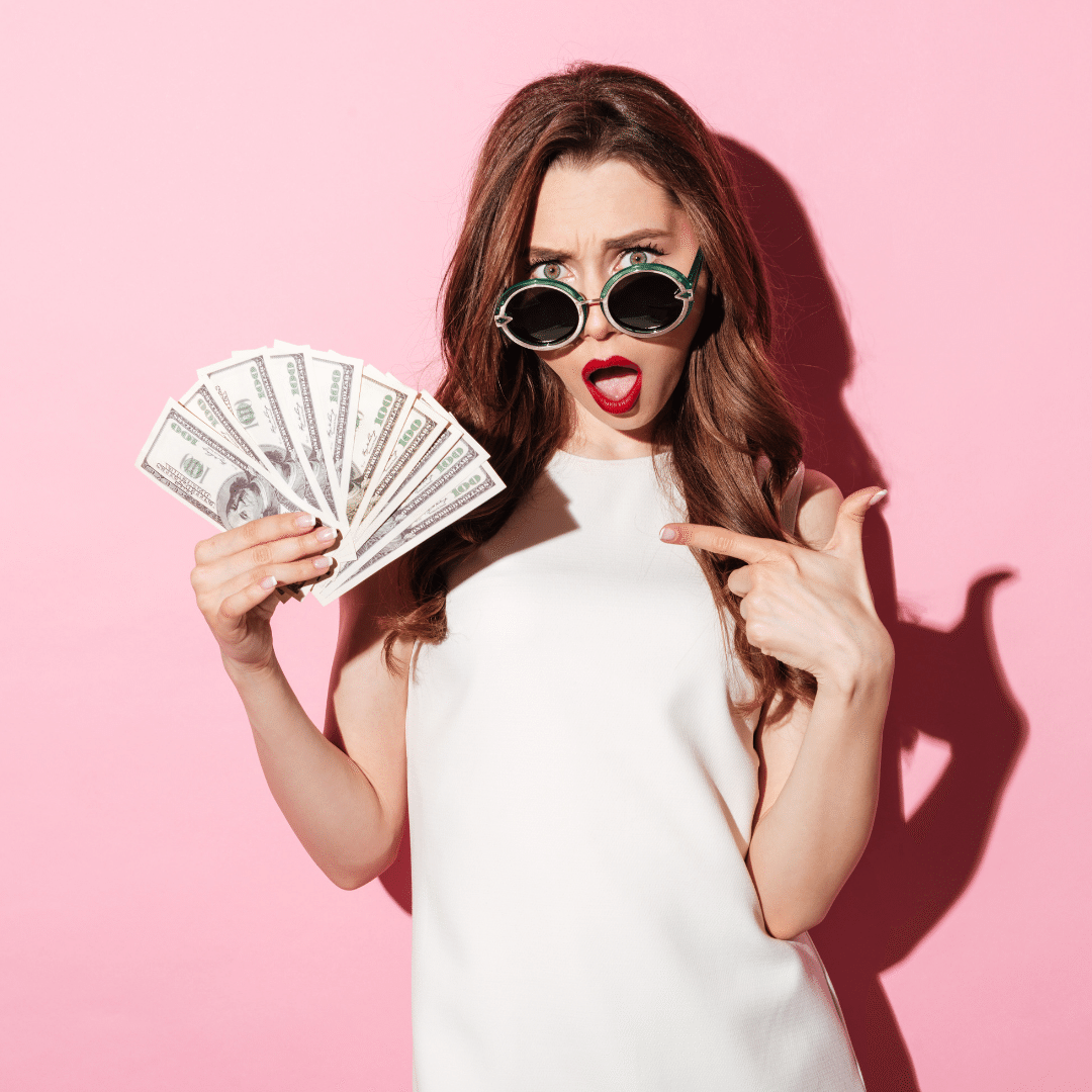 Woman holding cash and pointing at it