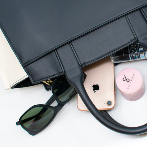 Minimalistic Makeup in Black Bag with Sunglasses and iPhone