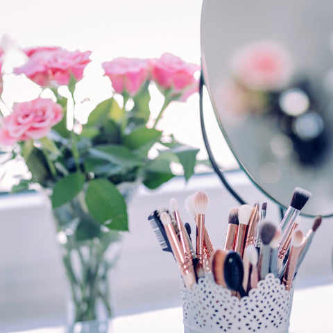 A container full of makeup brushes with a vase of roses in the background