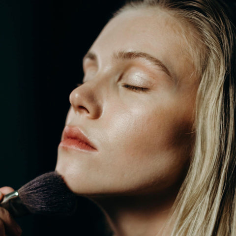 A woman applying makeup with a makeup brush.